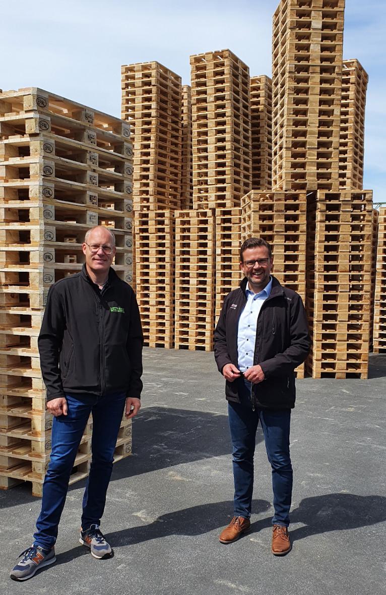 Geschäftsführer Tobias Lüffe-Baak und der Landtagsabgeordnete Raphael Tigges vor Stapeln von Holzpaletten (v.l.).